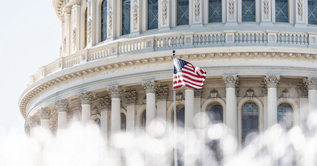 American flag in front of federal U.S capitol building