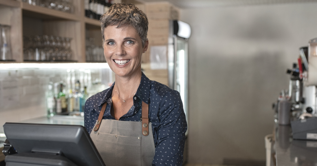 happy woman behind cashier in a franchise restaurant