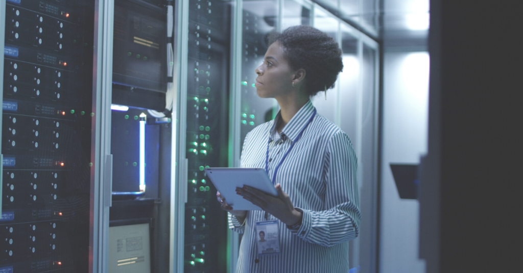 woman looking at technology in server room