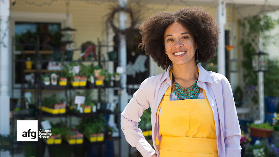 woman small business owner stands next to local shop